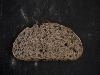 Dwarsdoorsnede zuurdesembrood - Crumbshot of sourdough on a black background